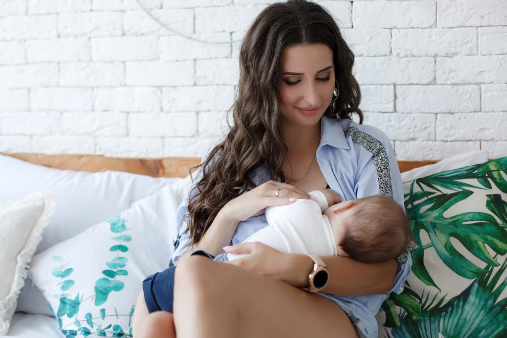 brown haired woman breastfeeding child