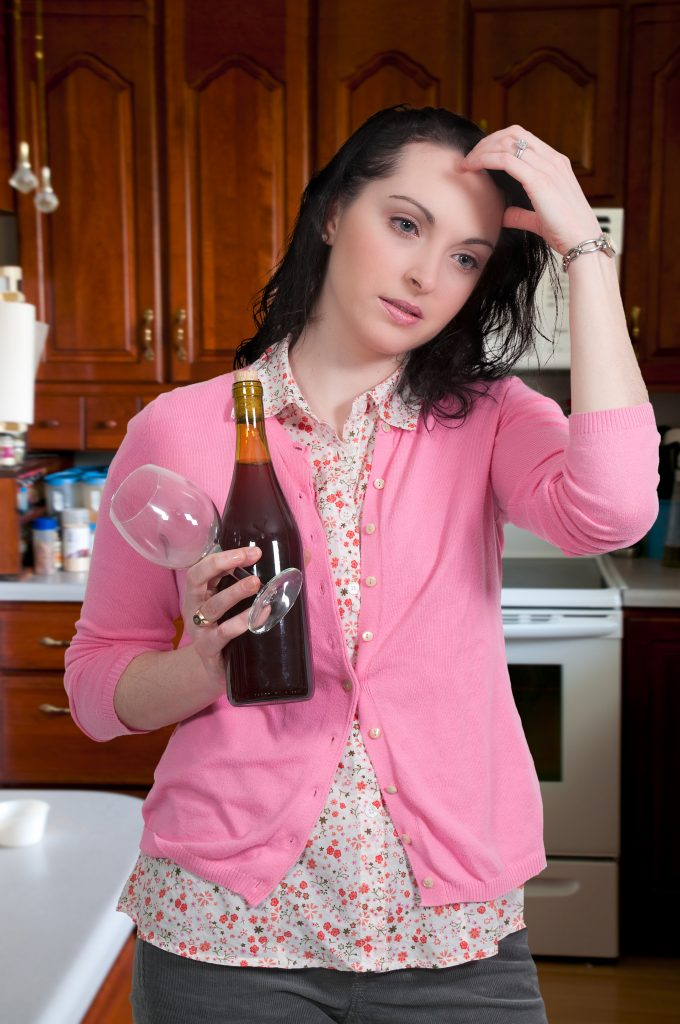 confused woman with bottle of alcohol