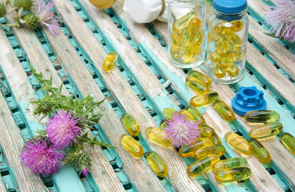 MILK THISTLE OIL IN SOFTGELS AND MILK THISTLE BLOSSOMS IN THE BACKGROUND